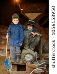Small photo of Happy farmer's children in back room with fodder grinder