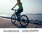 female cyclist riding mountain... | Shutterstock . vector #1056194999