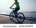 female cyclist riding mountain... | Shutterstock . vector #1056194999