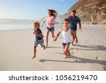 parents running along beach... | Shutterstock . vector #1056219470