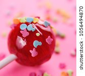 Small photo of pink round lollipop close-up on pink background. Color glaze in the form of small animal figures is strewed on a red candy.