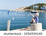 boy with binoculars on the pier.... | Shutterstock . vector #1056534140