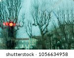Small photo of altered horizontal image of distorted trees without leaves with red traffic light