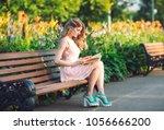 a young girl reading a book...   Shutterstock . vector #1056666200