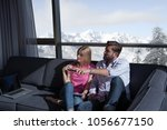 young couple sitting on sofa... | Shutterstock . vector #1056677150
