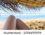 womans legs under the sunshade... | Shutterstock . vector #1056695954