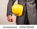 Small photo of engineer, builder hold yellow helmet, hard hat for workers security isolated on white background. male hand.