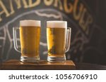 two mugs of chopp on the table | Shutterstock . vector #1056706910