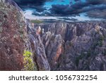 Small photo of Peering out onto the precipitous battlements and spires of Black Canyon of the Gunnison River National Park. Dark smoke like clouds move rapidly over the abysmal depths signaling a storm.