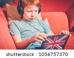 red haired boy sitting on the... | Shutterstock . vector #1056757370