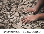 hand on ground cracked dry due... | Shutterstock . vector #1056780050