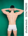 Small photo of young bodybuilder brunette posing on a colored paper background. athletic figure and relief muscles fitness trainer. emotional portrait of a student. dressed in beach boxer briefs. pumped up male ass
