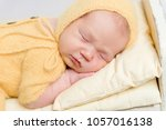baby dressed in knitted yellow... | Shutterstock . vector #1057016138