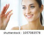 beautiful woman taking pill ...   Shutterstock . vector #1057083578