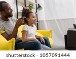father combing hair of daughter ... | Shutterstock . vector #1057091444