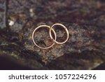 golden rings on wet stone after ...   Shutterstock . vector #1057224296