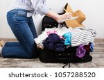 young girl casually packs black ... | Shutterstock . vector #1057288520