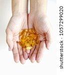 fish oil capsules in woman s... | Shutterstock . vector #1057299020