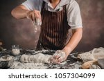 man preparing buns at table in... | Shutterstock . vector #1057304099