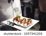 waiter carrying trays with food.... | Shutterstock . vector #1057341203
