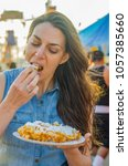 woman eating a delicious pastry ... | Shutterstock . vector #1057385660