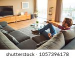 Small photo of Young caucasian man sitting in his amazing modern apartment's living room, watching TV and changing the channel with the remote he is holding in his hands.