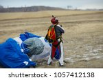 skydiver stands in the field... | Shutterstock . vector #1057412138