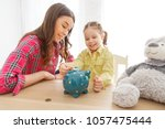 mother teaches her daughter to... | Shutterstock . vector #1057475444