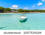 boat on crystal clear azure sea ... | Shutterstock . vector #1057524104