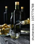 Small photo of Pouring olive oil into glass bowl on table