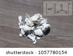 Small photo of Eggshell on the table, against the background of the chemical formula of calcium carbonate.Calcium carbonate, part of the egg shell. Used in everyday life to alkalize the soil in gardening.
