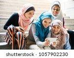 islamic women sharing smartphone | Shutterstock . vector #1057902230
