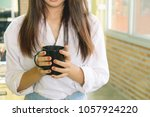 female holding a mug of coffee.   Shutterstock . vector #1057924220