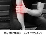 elbow pain. man in the park... | Shutterstock . vector #1057991609