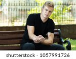man holding sore wrist in his... | Shutterstock . vector #1057991726