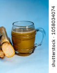 Small photo of Popular Indian/Asian Ganne ka ras or Sugar cane or Saccharum officinarum juice in a transparent glass with raw sugarcane isolated on white.