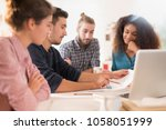 in the office. meeting around a ... | Shutterstock . vector #1058051999