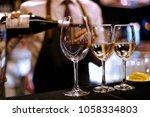 barman pours white wine | Shutterstock . vector #1058334803