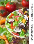 Small photo of Dish of Lettuce salad mixed with sliced common mushroom (Agaricus bisporus), tomatoes and carrots