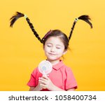 smiling little girl enjoying... | Shutterstock . vector #1058400734