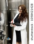 Small photo of Young woman manageress is standing in front of steel cylinder of large stainless steel tank in chemical manufacturing. She writes the current status of the unit.