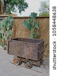 Small photo of An old mining ore cart sits in front of a huge prickly pear cactus and against an adobe wall.