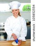 Female chef kneading bread dough in a kitchen - stock photo