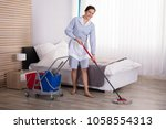 young female housekeeper... | Shutterstock . vector #1058554313