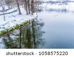 park in winter with a lake snow ... | Shutterstock . vector #1058575220