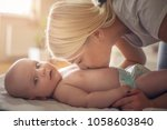 happy young mother kissing her... | Shutterstock . vector #1058603840