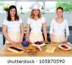 Team of confident chefs presenting snacks. Fresh food decorated on table - stock photo