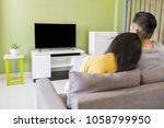 happy asian couple watching a... | Shutterstock . vector #1058799950