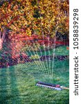 Small photo of Oscillating sprinkler watering fresh mown lawn and flower bed in the evening autumn garden