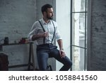 handsome stylish man in suit is ... | Shutterstock . vector #1058841560